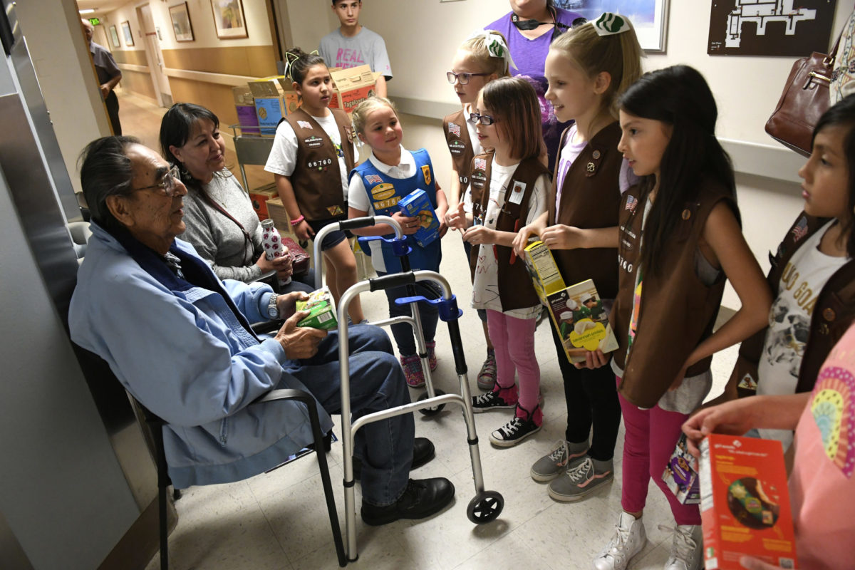 DENVER, CO - APRIL 2: Girl Scout Genevieve Miotto, 7, middle with glasses, and her troop mates give a box of Girl Scout cookies to Korean War veteran James Salazar, left, while his daughter Jacqueline, second from left, watches with delight at the Denver VA Medical Center on April 2, 2018 in Denver, Colorado. Almost 40 girl scouts, from a different Colorado troops, and their troop leaders delivered thousands of packages of free Girl Scout cookies to veterans and staff at the medical center. Making the world a better place is central to the Girl Scout mission. The cookies were purchased as part of Girl Scouts' Hometown Heroes/Gift of Caring program. Girl Scouts of Colorado is 32,000 strong, more than 22,000 girls and 10,000 adults who believe in the power of every G.I.R.L or Go-getter, Innovator, Risk-taker, Leader. (Photo by Helen H. Richardson/The Denver Post)