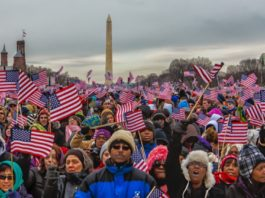 Americans waving flags in front of the washington monument